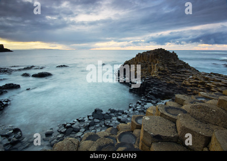 Calm waters at sunset over the famous Giant's Causeway UNESCO world heritage site in Northern Ireland. - Stock Photo