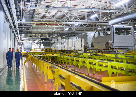 Workers walking in car factory - Stock Photo
