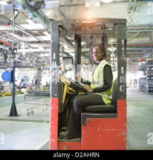 Apprentice lift operator in car factory - Stock Photo
