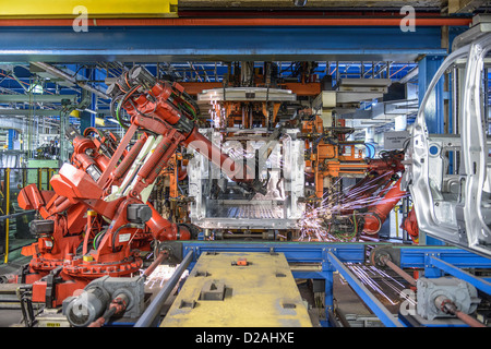 Robots welding van body in car factory - Stock Photo
