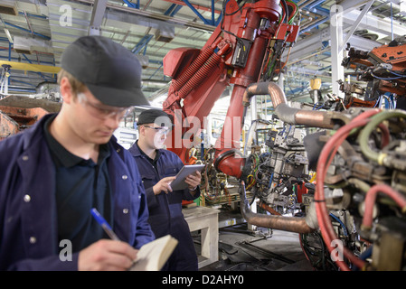 Apprentices with robots in car factory - Stock Photo