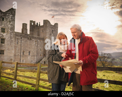 Older couple reading map by castle - Stock Photo