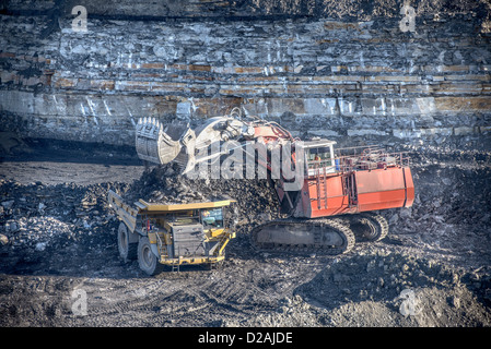 Trucks and digger at surface coal mine - Stock Photo