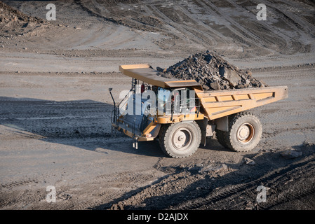 Trucks with coal rocks at surface mine - Stock Photo