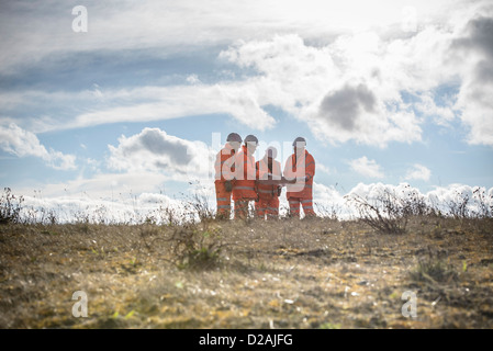 Workers reading blueprints in field - Stock Photo