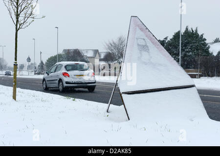 Chester UK. 18th Jan, 2013. A car travels past a snow covered sign warning of slippery road conditions. - Stock Photo