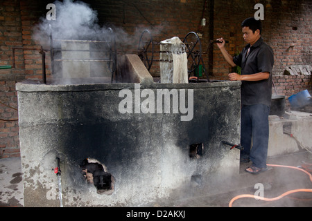 A worker pulls out wool of a tank of hot dye. The dye is heated by kerosene boilers and it is hot and dangerous - Stock Photo