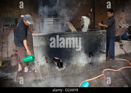 Workers pull out wool of a tank of hot dye. The dye is heated by kerosene boilers and it is hot and dangerous work. - Stock Photo