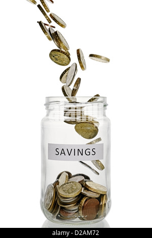 Savings Jar With Coins Pouring Into It, UK Currency. - Stock Photo