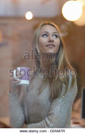 Woman drinking coffee behind window - Stock Photo