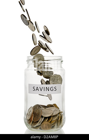 Savings Jar With Coins Pouring Into It, US Currency. - Stock Photo