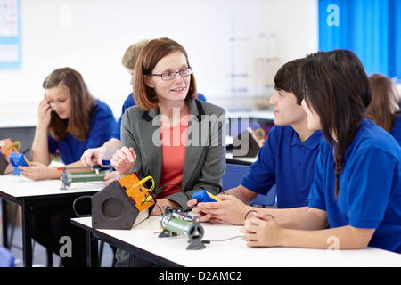 Teacher with students in science class - Stock Photo