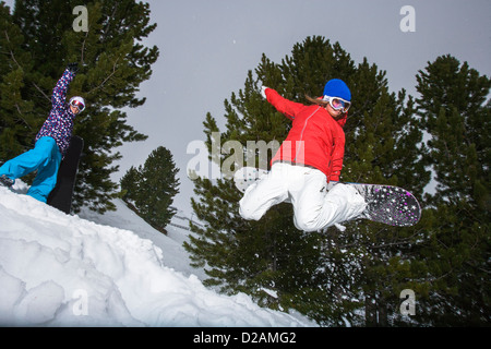 Snowboarder jumping on snowy slope - Stock Photo