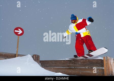 Snowboarder sliding on wooden fence - Stock Photo