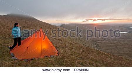 Hiker at campsite overlooking landscape - Stock Photo