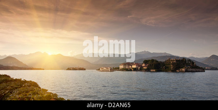 Sun rising over rural village and lake - Stock Photo