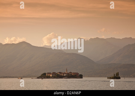 Mountains over rural village and lake - Stock Photo