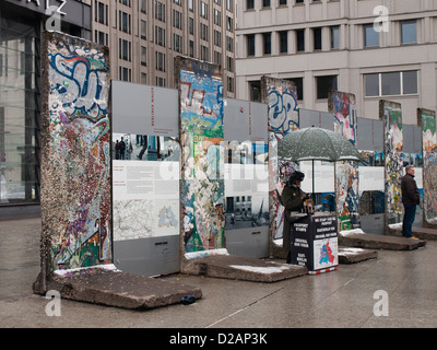 Potsdamer Platz in Berlin Germany on a gloomy winters day. Parts of the wall, street vendor selling East German - Stock Photo