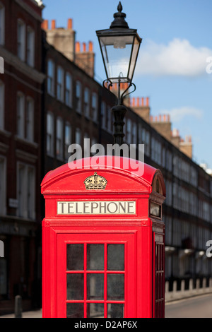 Red telephone box on city street - Stock Photo