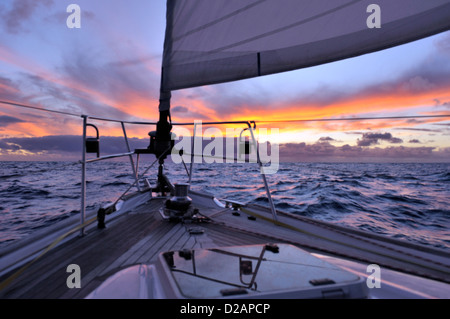 Squall ahead on the horizon at sunset seen over the bow of a cruising yacht sailing offshore into the sunset from - Stock Photo