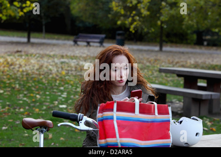Woman sitting with bicycle in park - Stock Photo