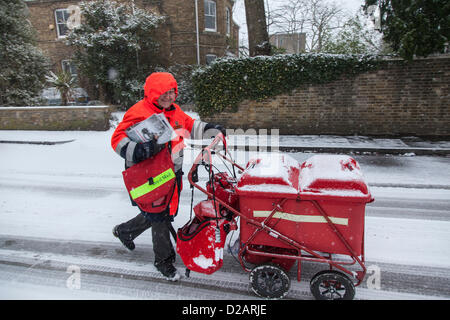 Postman delivering mail in winter - Stock Photo