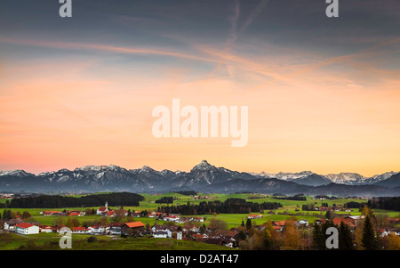 Clouds over village and mountains - Stock Photo