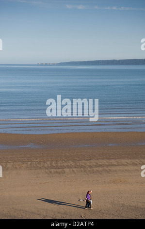 Couple strolling on quiet sandy beach on sunny summer evening by calm flat sea under blue sky - South Bay, Scarborough, - Stock Photo