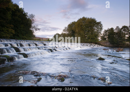 Scenic, evening, rural landscape of water flowing & tumbling over & down weir steps - River Wharfe, Burley in Wharfedale, - Stock Photo