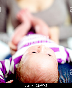 View from the top of the head of a tiny baby lying on its back on its mothers lap - Stock Photo