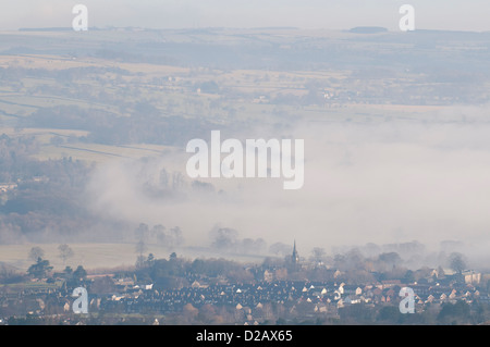 Long-distance, foggy early morning view over scenic rural valley & village shrouded in mist or fog - Burley in Wharfedale, - Stock Photo