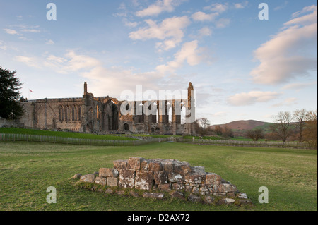 View from south of sunlit, ancient, picturesque monastic ruins of Bolton Abbey & priory church, in scenic countryside - Yorkshire Dales, England, UK.