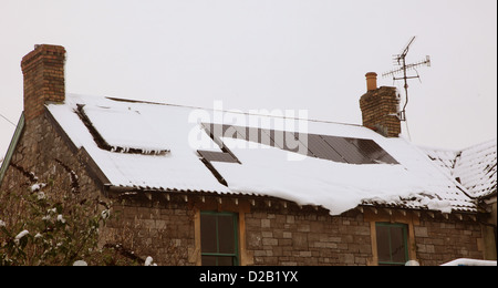 Snow sliding off solar panels during the winter of January 2013 in the village and gorge of Cheddar in Somerset, - Stock Photo