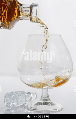 High speed frozen drops of pouring brandy from a crystal decanter into a snifter glass on white background - Stock Photo