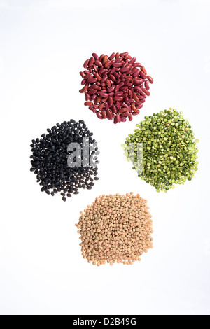 Four piles of dried peas, lentils, black beans, and kidney beans on white background. - Stock Photo