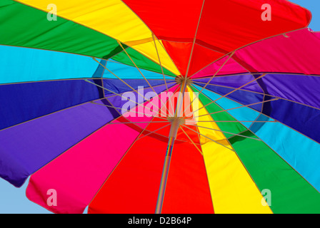 Close-up view from under a bright rainbow colored umbrella - Stock Photo