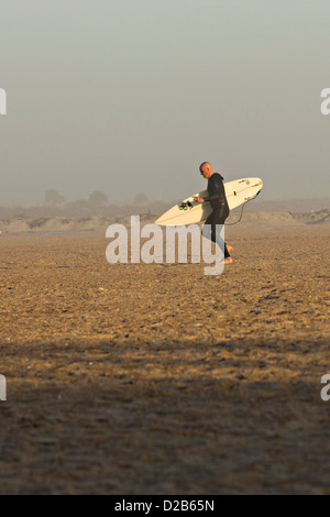 A surfer walks back from the water in St Augustine Beach, Florida. - Stock Photo