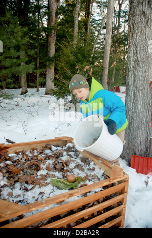 5 Year Old And 8 Year Old Girls Dumping Food Scraps Into Compost Bin - Stock Photo