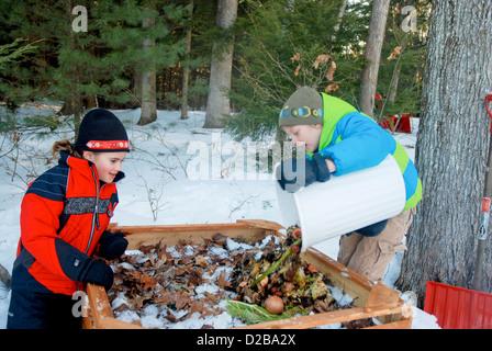 Girls Dumping Food Scraps Into Compost Bin - Stock Photo