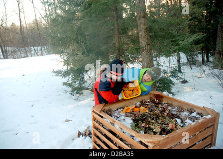 Girl Dumping Food Scraps Into Compost Bin - Stock Photo