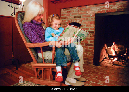 5 Year Old Girl Reading With Grandmother By Fire - Stock Photo