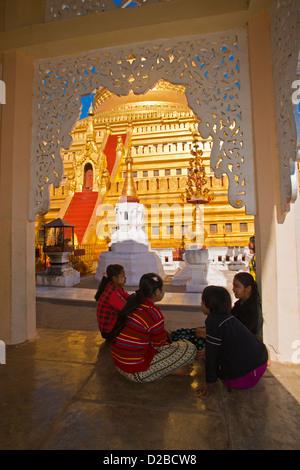 Pilgrims sit or walk around the Shwezigon Paya Golden Pagoda in Paya, Bagan, Myanmar. - Stock Photo