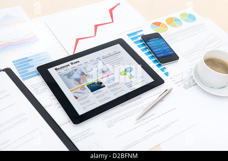 Modern business workplace with business news website on a digital tablet and some charts and graphs on a desktop - Stock Photo
