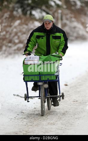 Berlin, Germany, the postman PIN AG is proceeding bike along a snowy sidewalk