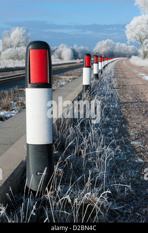 Bollards along edge of the guided busway or bus track between St Ives and Cambridge Cambridgeshire UK on a cold - Stock Photo