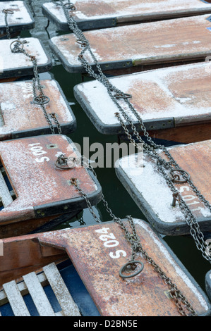 Punts in the snow in winter on the River Cam Quayside Cambridge UK - Stock Photo