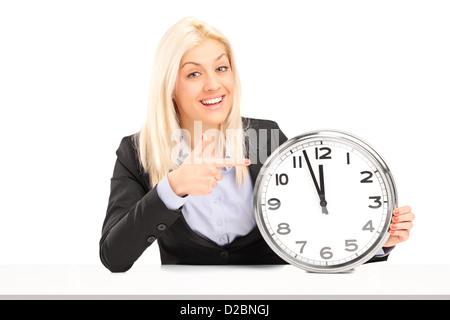 Blond businesswoman sitting and pointing on a wall clock, isolated on white background - Stock Photo