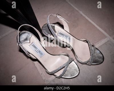 A pair of Jimmy Choo Stilettos abandoned under a chair at the end of a wedding party. - Stock Photo