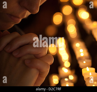 Woman praying in church cropped part of face and hands closeup portrait