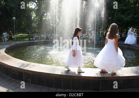 Gomel, Belarus, bridesmaids and wedding couple at the Fountain - Stock Photo